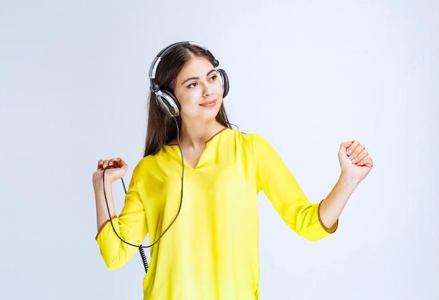 Mädchen mit kopfhörern, die das kabel halten und tanzen.