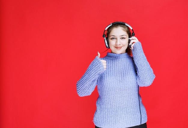 Mädchen mit kopfhörern, die die musik genießen und positives handzeichen zeigen.