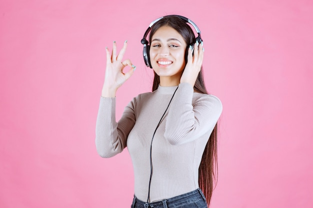 Mädchen mit kopfhörern, die die musik hören und ihren genuss zeigen