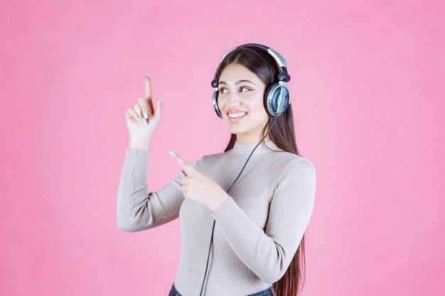 Mädchen mit kopfhörern, die die musik hören und nach oben zeigen