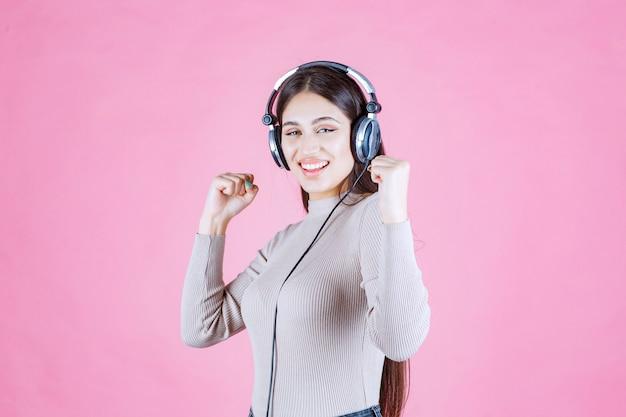 Mädchen mit kopfhörern, die die musik hören und sich glücklich fühlen