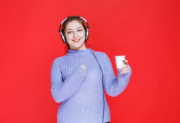 Mädchen mit kopfhörern, die eine einwegtasse kaffee halten.