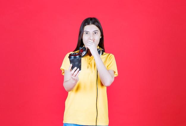 Mädchen mit kopfhörern, die einen schwarzen einwegbecher halten und sieht verängstigt und verängstigt aus.