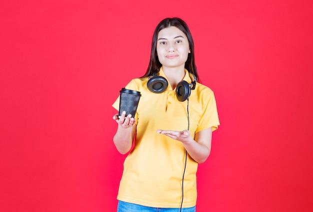 Mädchen mit kopfhörern, die einen schwarzen einwegbecher halten