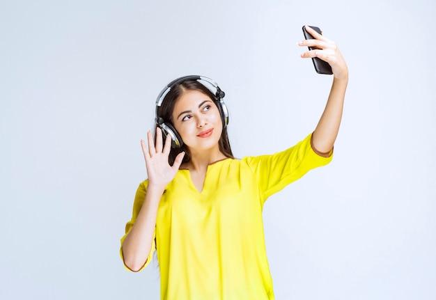 Mädchen mit kopfhörern, die ihr selfie machen oder einen videoanruf tätigen.