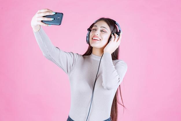 Mädchen mit kopfhörern, die ihr selfie nehmen