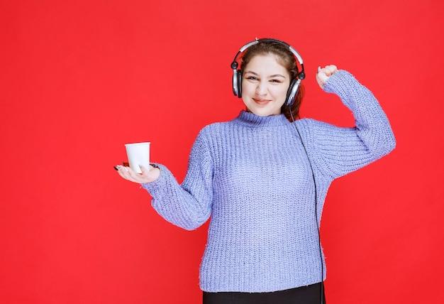 Mädchen mit kopfhörern, die kaffee trinken und sich mächtig fühlen.