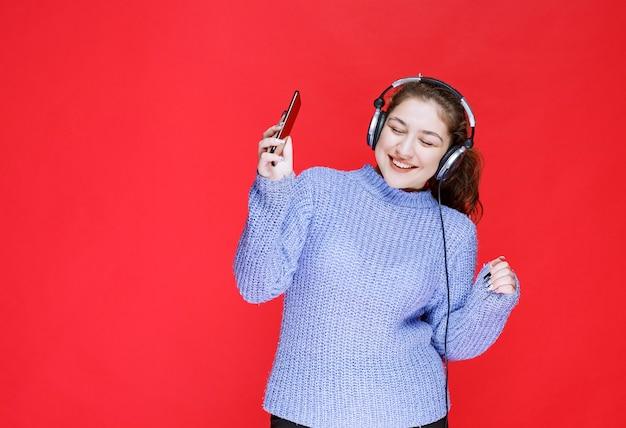 Mädchen mit kopfhörern, die musik an ihrem smartphone einstellen und es genießen.