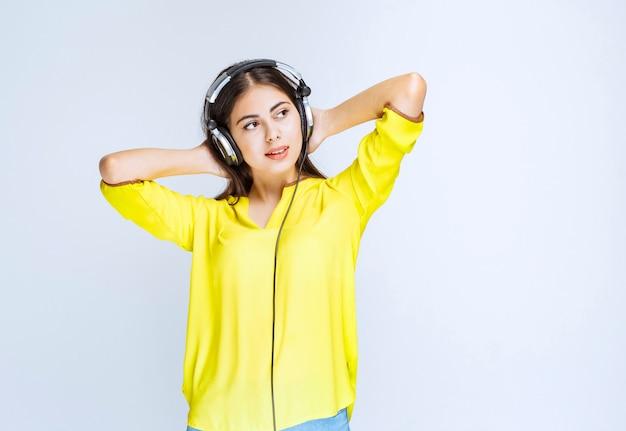 Mädchen mit kopfhörern, die ruhig bleiben und die musik genießen.