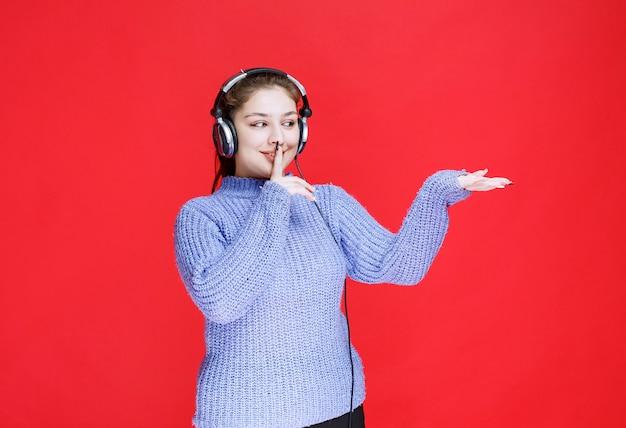 Mädchen mit kopfhörern, die um stille bitten, da sie nicht gut hören kann.