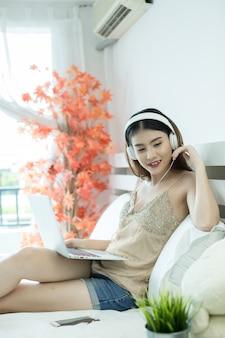 Mädchen mit kopfhörern hörend musik in einem laptop auf dem bett zu hause