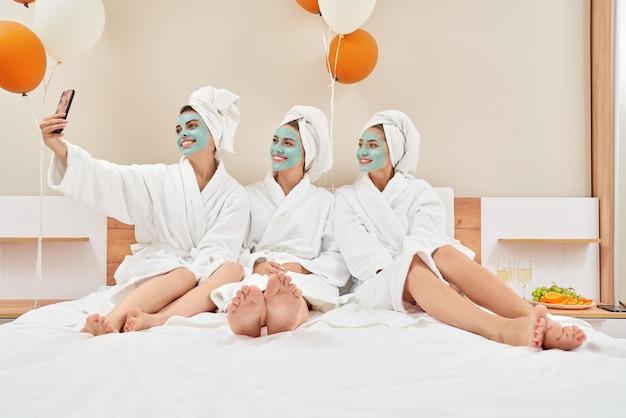 Mädchen mit kosmetischen masken, die selfie im schlafzimmer nehmen.