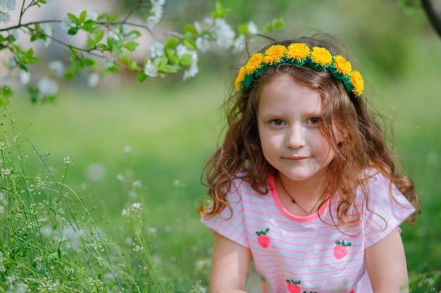 Mädchen mit kranz des löwenzahns auf kopf im park mit zweigen der kirschblüten.