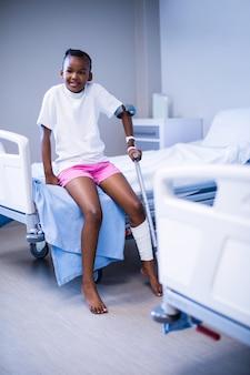 Mädchen mit krücken, die auf krankenhausbett in der station sitzen