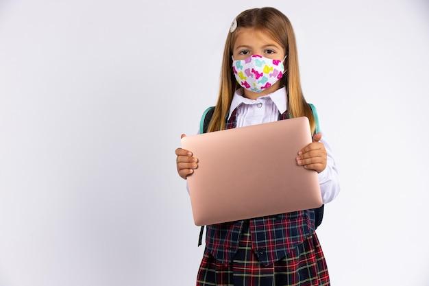 Mädchen mit kundenspezifischer gesichtsmaske, die nach covid-19-quarantäne und sperrung zurück zur schule geht. schulform und laptop in der hand.