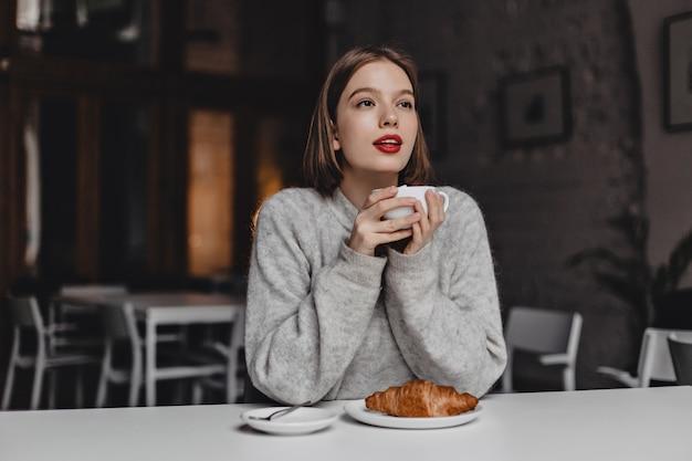 Mädchen mit kurzen haaren und rotem lippenstift, gekleidet in warmen pullover, der tee mit croissant im gemütlichen café genießt.