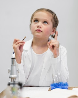 Mädchen mit laborkittel und mikroskop