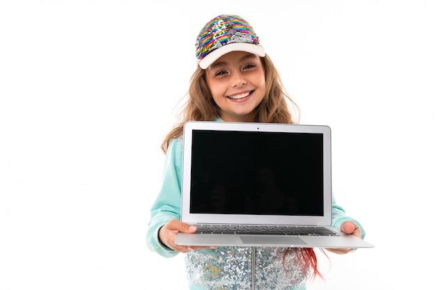Mädchen mit langen blonden haaren gefärbt mit spitzen rosa, in glänzend weißer mütze, hellblauem sportanzug, gürteltasche steht und hält einen laptop in ihren händen