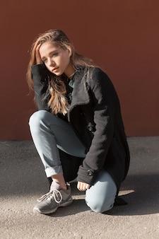 Mädchen mit langen blonden haaren im schwarzen mantel, jeans und turnschuhen sitzt auf dem bürgersteig.