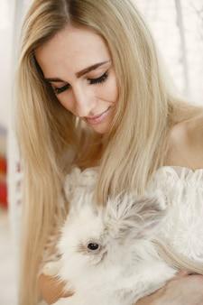 Mädchen mit langen blonden haaren mit einem weißen kaninchen in ihren armen.