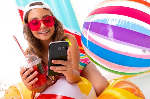 Mädchen mit langen gekreuzigten haaren in sonnenbrille und badeanzug sitzt auf aufblasbaren matratzen mit frischem fruchtcocktail und unterhält sich mit freunden lokalisiert auf einem weißen hintergrund