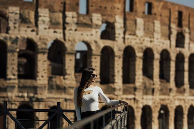 Mädchen mit langen haaren in stilvollen kleidern, die nahe kolosseum in rom aufwerfen