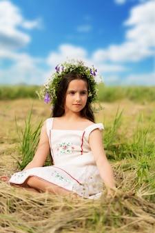 Mädchen mit langen haaren mit einem blumenkranz auf dem kopf sitzt im heu