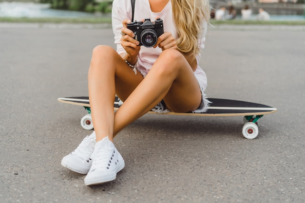 Mädchen mit langen haaren mit skateboard fotografieren vor der kamera. straße, aktiver sport