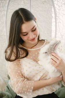 Mädchen mit langen haaren. weißes kaninchen in den armen des mädchens.