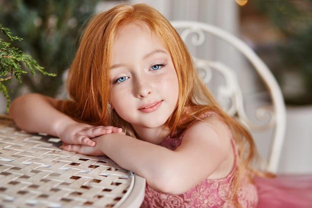 Mädchen mit langen roten haaren in einem rosa kleid, das am tisch sitzt. karnevalsfeiertag geburtstag. porträt eines fröhlichen rothaarigen mädchens mit großen blauen augen