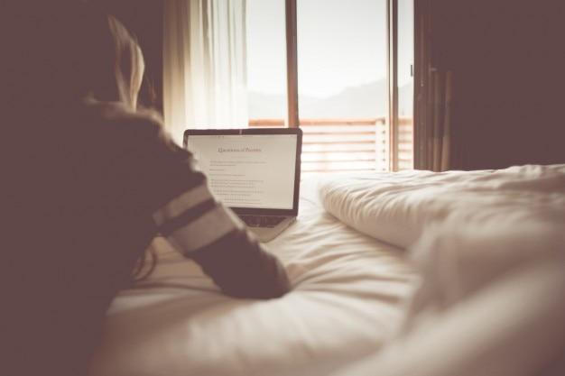 Mädchen mit laptop auf ihrem bett
