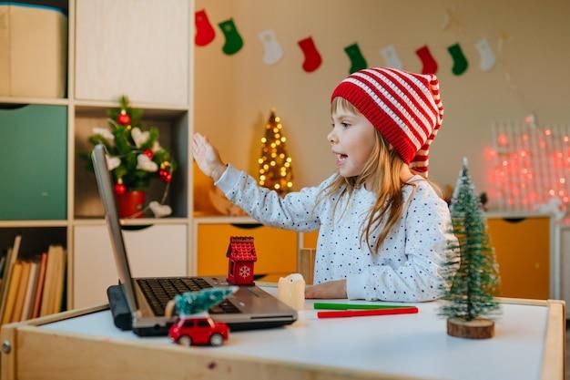 Mädchen mit laptop für videoanruf im kinderzimmer in der weihnachtszeit