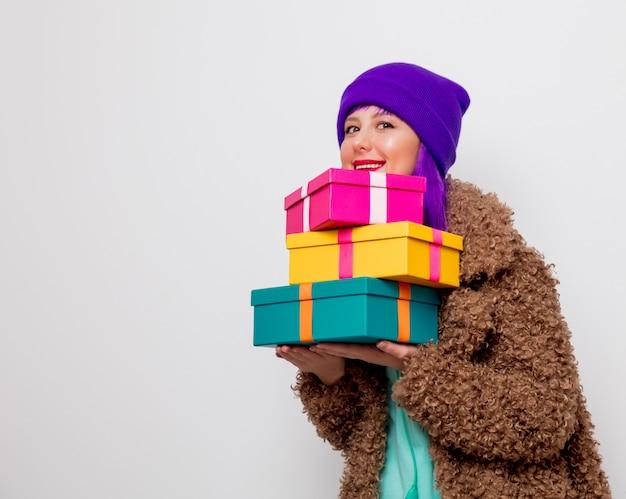 Mädchen mit lila haaren in jacke mit geschenkboxen
