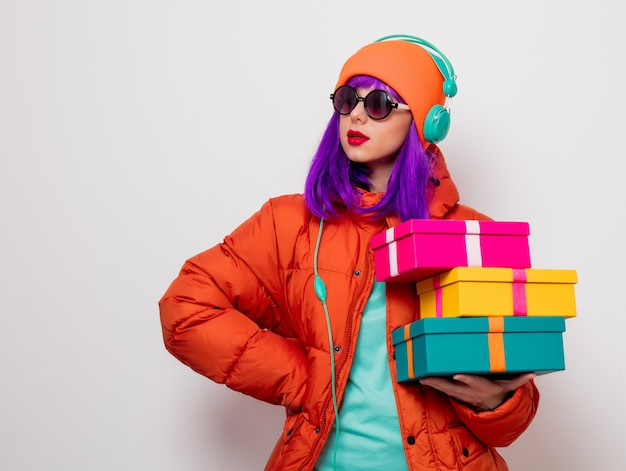Mädchen mit lila haaren mit kopfhörern und geschenken