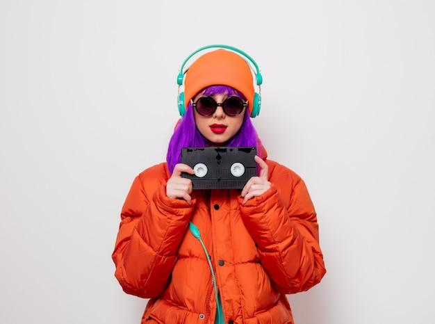 Mädchen mit lila haaren mit kopfhörern und vhs