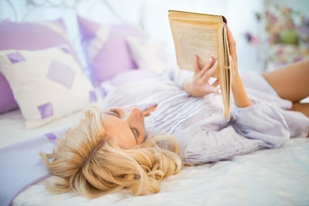 Mädchen mit lockigen blonden haaren im lila kleid liegt im bett auf dem rücken und hält buch in händen