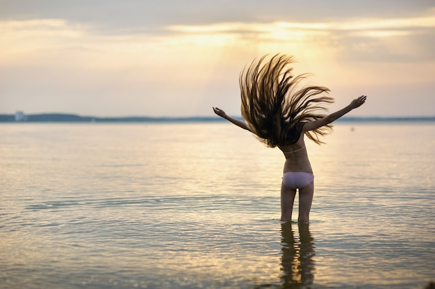 Mädchen mit losen haaren auf dem meer bei sonnenuntergang