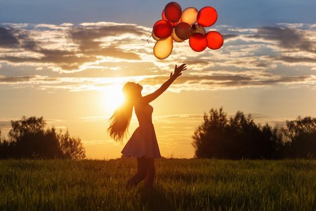 Mädchen mit luftballons bei sonnenuntergang