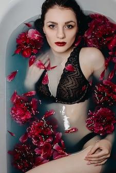 Mädchen mit make-up in bh liegt und genießt im bad mit pfingstrosen