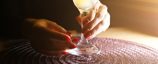 Mädchen mit margarita-cocktail auf dem tisch im restaurant. alkoholische getränke. schöne hände.