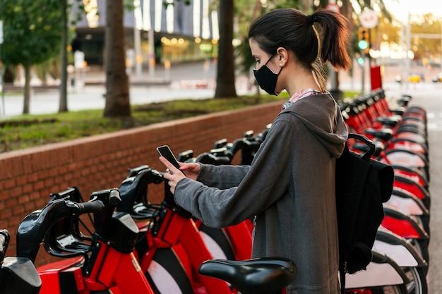 Mädchen mit maske, die ein fahrrad mit dem telefon entsperrt