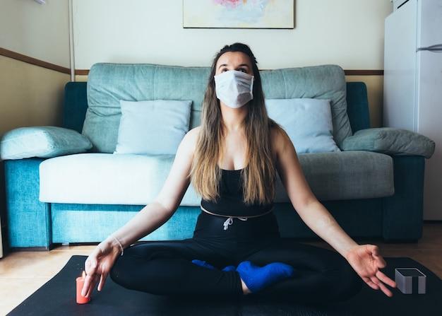 Mädchen mit maske, die meditation zu hause tut.