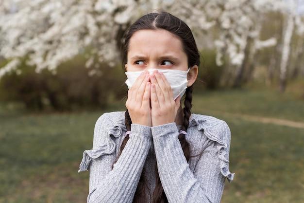 Mädchen mit maske, die weg schaut