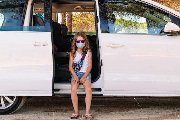 Mädchen mit maske im gesicht und rosa sonnenbrille sitzt auf der tür im auto mit offener tür, während sie mitten in der covid19-coronavirus-pandemie in den urlaub fährt