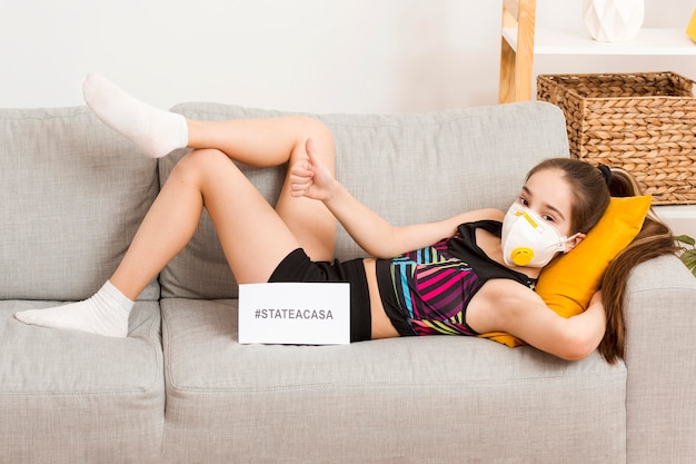 Mädchen mit maske sitzt auf der couch