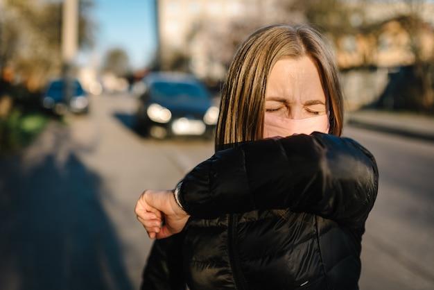 Mädchen mit maske während covid-19-pandemiehusten auf der straße. die gefahren des coronavirus. risiko der ausbreitung einer infektion. bedeckte nase und mund, nieste gebeugten ellbogen. frauenhusten in der armprävention.