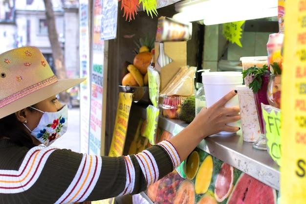 Mädchen mit maskengesicht trinkt fruchtsaft