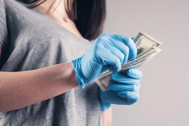 Mädchen mit medizinischem handschuh, der geld hält