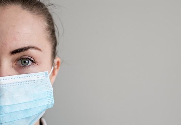 Mädchen mit medizinischer maske, um sie vor viren zu schützen. coronavirus-pandemie. frau mit maske stehend. menschen, die ins krankenhaus eingeliefert, diagnostiziert und häufig in carantine (isolation) gebracht werden, um die verbreitung von corona zu stoppen.