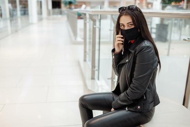 Mädchen mit medizinischer schwarzer maske und handy in einem einkaufszentrum. coronavirus pandemie. eine frau mit einer maske steht in einem einkaufszentrum. mädchen in einer schutzmaske kauft im einkaufszentrum ein